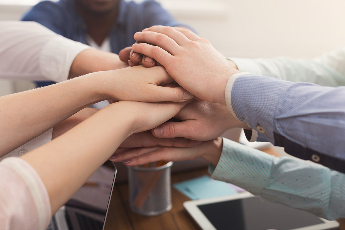 teamwork-and-teambuilding-people-connect-hands-PBEQDRJ